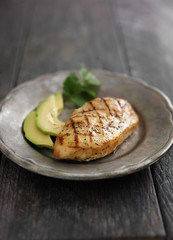 grilled chicken with cilantro and avocado on metal plate