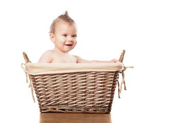 Happy little baby boy sitting in a wicker basket