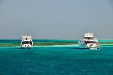 Две белые яхты в море около коралловых рифов