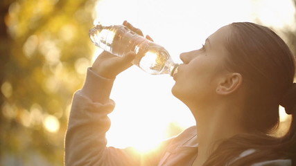 Sportswoman Drinking Water Against Sunbeams