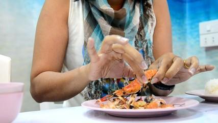 Women peeling shrimp or prawn grilled