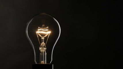 Light bulb over black background. 4K, UHD