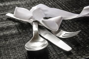 Besteck set mit weißer Schleife auf schwarzem Tischset