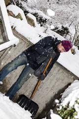 Mann räumt Schnee von einer Treppe