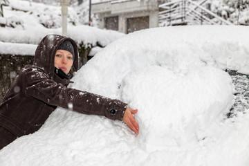 Frau formt aus Schnee auf Scheibe ein Herz