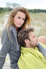 Couple sitting on sand - windy autumn day on the beach