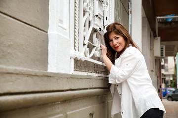 Mature woman standing at metal window...