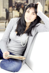 Beautiful woman sitting on sofa in the city with tablet