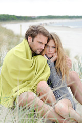 Couple relaxing on windy autumn day on the beach - sea, blanket