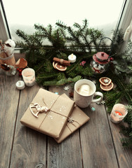 window on a wooden window sill branches green tree gifts and cup