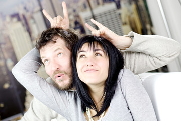 Funny couple making horns gesture one to another