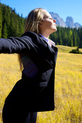Blonde business woman enjoying air in the mountain