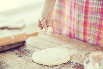closeup of female hand sprinkling dough with flour
