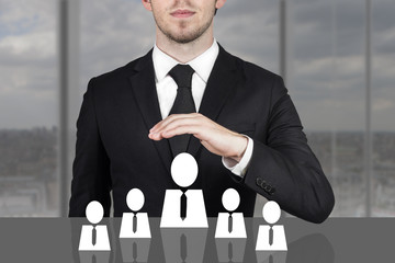 businessman holding protective hand above employee staff