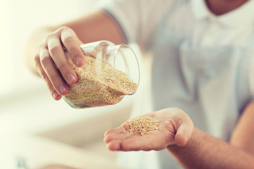 close up of male emptying jar with quinoa