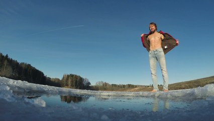 Young man swimming in the winter pond's ice hole on sunny day. F