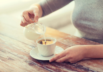 close up of female pouring milk into coffee