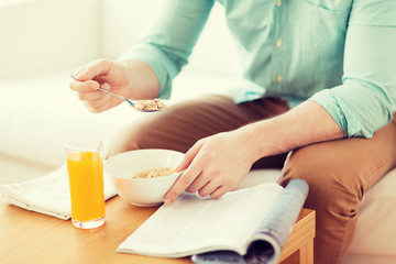 close up of man with magazine eating breakfast