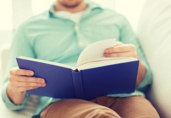 close up of man reading book at home