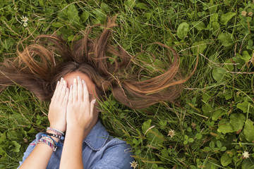 Girl lying on green grass and covering his face with his hands.