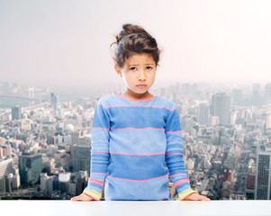 sad little girl over city background