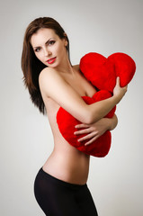 Young beautiful woman with red hearts in her arms