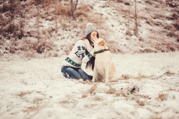 Cute young woman playing with dog in winter park