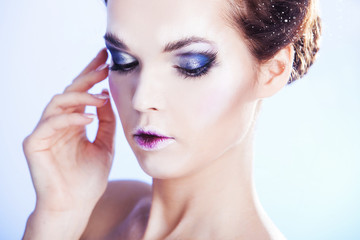 Close up portrait of woman with smoky eyes over blue winter