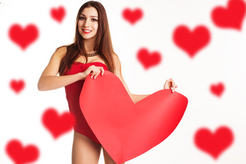 Beautiful woman is holding big paper red heart