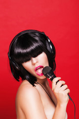 Woman listening to music on headphones enjoying a singing