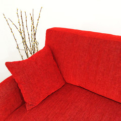 Red velvet sofa and willow branches in a vase