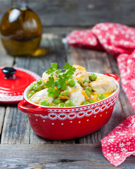 Chicken stew with peas in cream sauce in a red pot