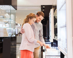 happy couple choosing engagement ring in mall