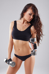 Pretty athletic woman exercising with dumbbells