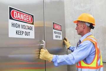 Engineer at electric power plant opening high voltage area doors