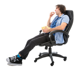 Lazy man sitting in armchair eating pop corn