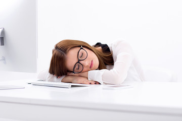Beautiful business woman sleeping on the table at her workplace