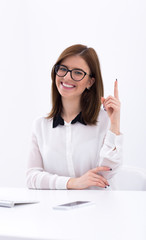 Happy young businesswoman pointing finger up