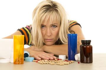 woman head down looking lots of pills