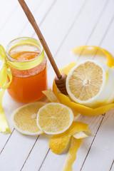 Honey in glass jar and lemons