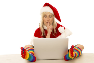 woman in Santa hat and colored socks with laptop shhh