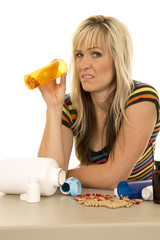 woman with pill bottle and lots of pills spilled