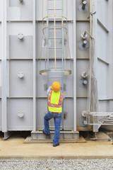 Engineer climbing ladder of gas turbine