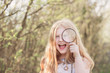 portrait of a cute young girl looking through magnifying glass a