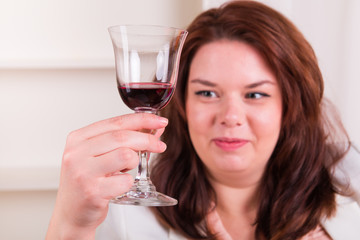 Plump and cheerful woman holding a glass of wine