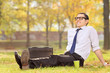 Businessman relaxing seated on a grass in park