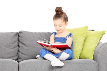 Adorable little girl reading a book on sofa