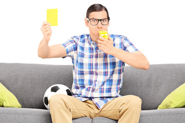 Angry football fan holding a yellow card seated on couch