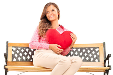 Beautiful girl holding a red heart seated on a wooden bench