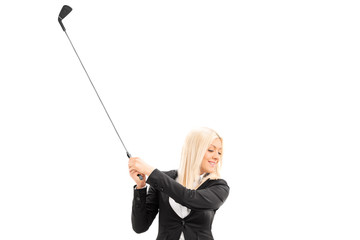 Businesswoman swinging a golf club